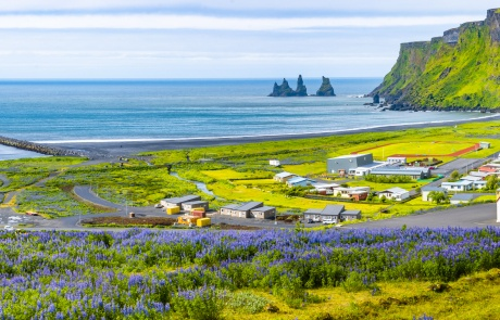 View of basalt stacks Reynisdrangar, black sand beach, church and city of Vik, Iceland