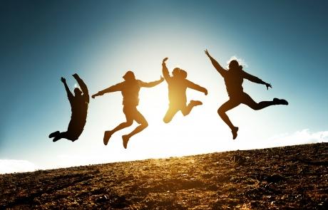 Four jumping silhouettes friends against sun