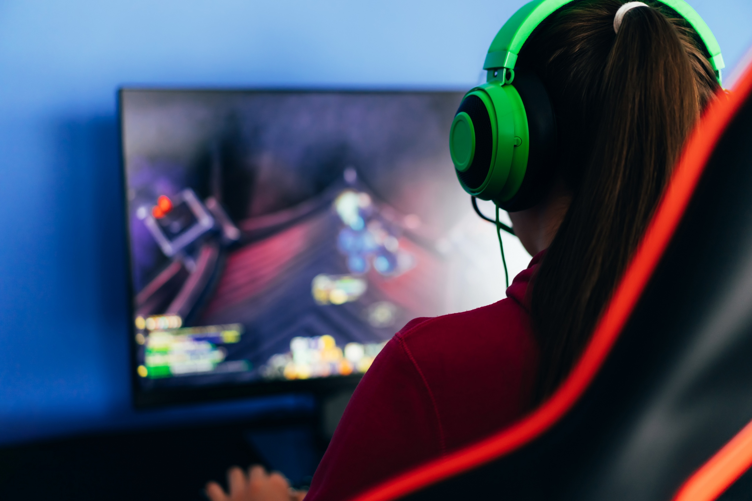 A young girl playing a computer game on professional armchair against monitor in green headphones, live stream, esports