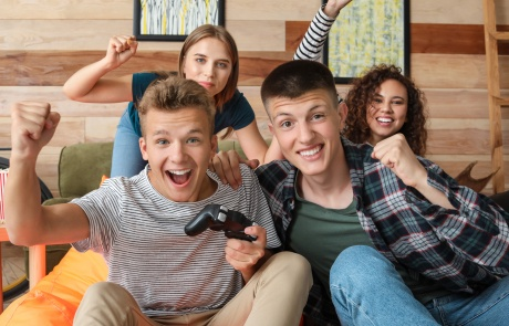 Teenagers playing video game at home