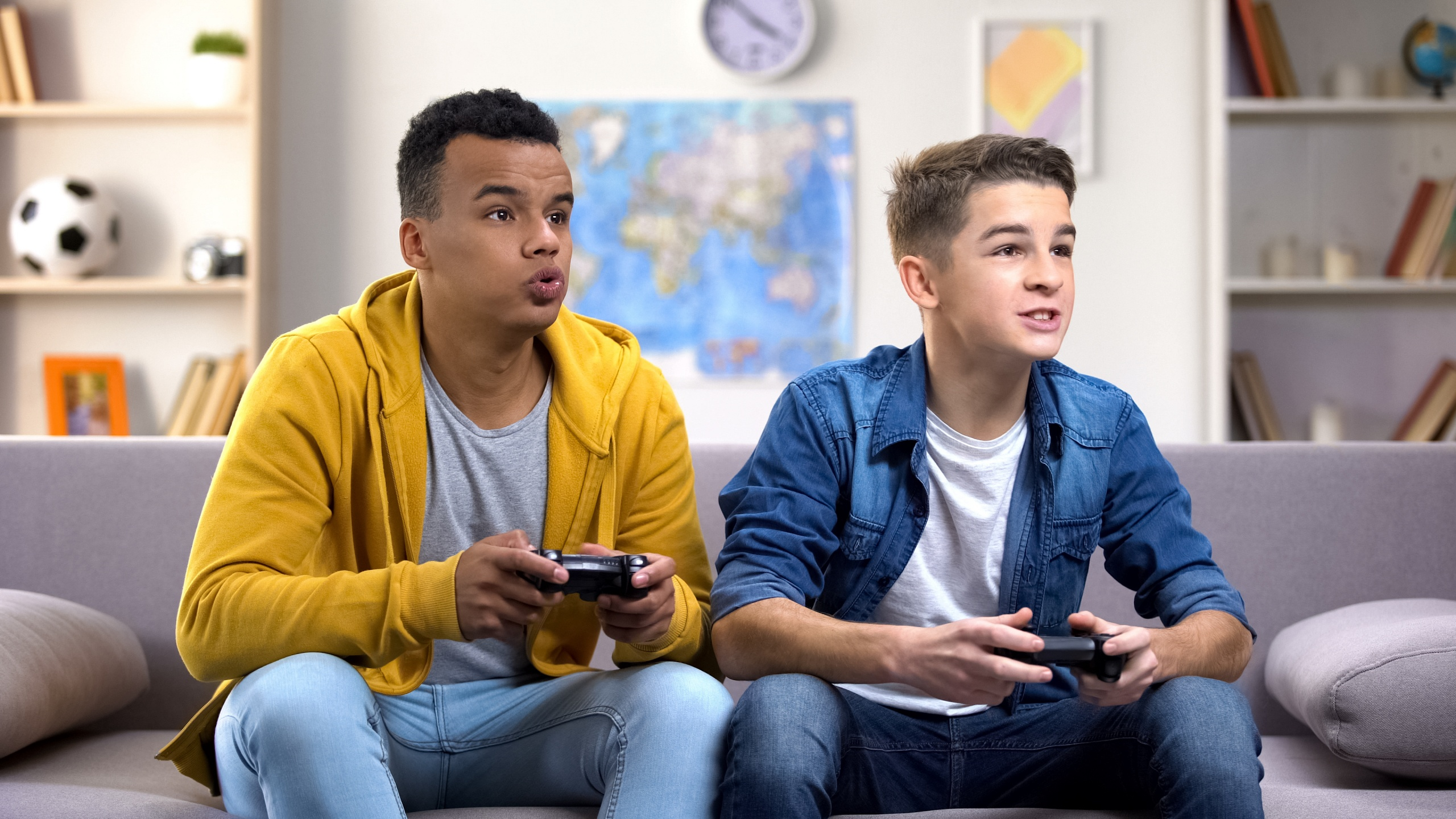 Excited multiethnic teen friends enjoying video games, free time at home