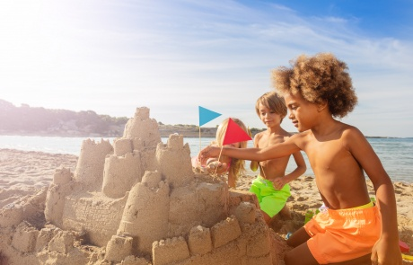 Happy kids decorating sandcastle towers with flags